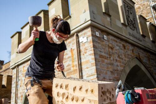 Vor historischer Kulisse arbeitet Steinmetzin Marie-Elaine Boos nach traditioneller Handwerkskunst.